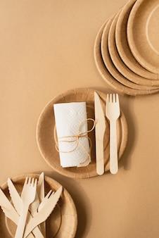 Brązowa jednorazowa torba i zastawa stołowa, talerz i drewniany widelec, nóż na brązowej powierzchni