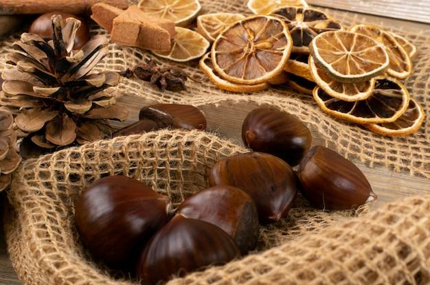 Brązowa jesienna martwa natura z kasztanami, laskami cynamonu, suszonymi cytrynami i szyszkami sosnowymi, widok z góry i płasko leżak