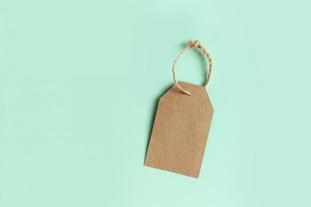 Brązowa kartonowa metka na pastelowej zieleni, widok z góry. zarejestruj sprzedaż.
