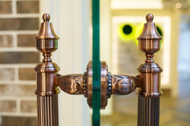Brązowa klamka na szklanych drzwiach. przezroczyste drzwi