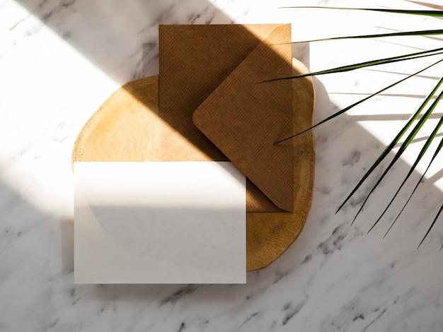 Brązowa koperta z białym pustym miejscem na drewnianym talerzu na marmurowym tle z zielonymi liśćmi