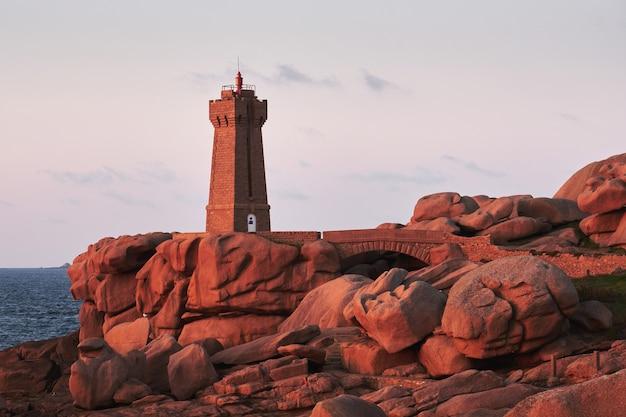 Brązowa latarnia morska na skalnym klifie, w pobliżu zbiornika wodnego