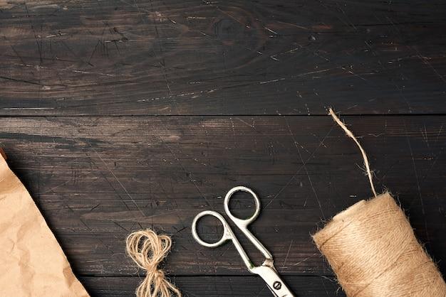 Brązowa nić skręcona w szpulę i zabytkowe metalowe nożyczki