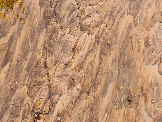 Brązowa powierzchnia ziemi. zamknij się naturalne tło, rozmyte mokrej gliny