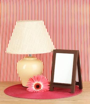 Brązowa ramka na zdjęcia i lampa na drewnianym stole na czerwonej ścianie w paski