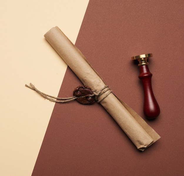 Brązowa rolka papieru zapieczętowana woskową pieczęcią, widok z góry, z bliska