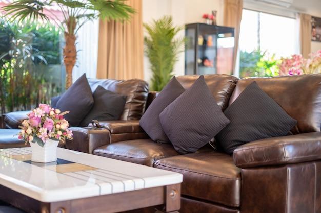 Brązowa skórzana kanapa i czarne poduszki