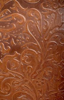 Brązowa skórzana okładka książki lub czasopisma z ozdobnym ornamentem roślinnym