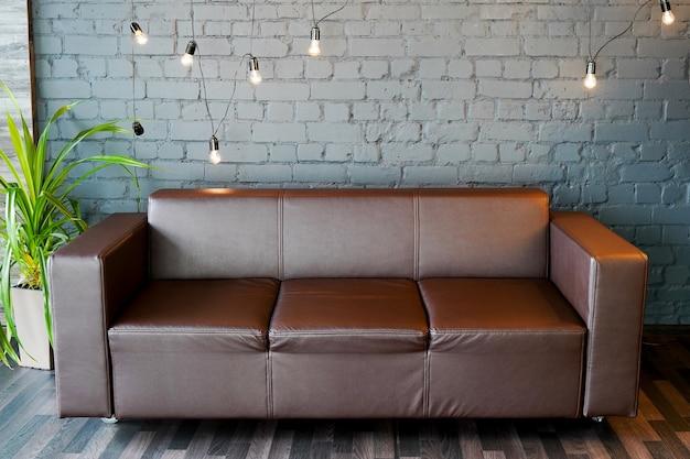 Brązowa skórzana sofa i kamienna ściana z nowoczesnym oświetleniem, koncepcja wnętrza biura