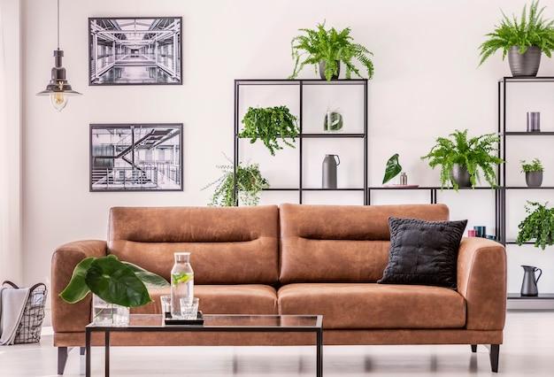 Brązowa skórzana sofa pośrodku eleganckiego salonu z koncepcją miejskiej dżungli