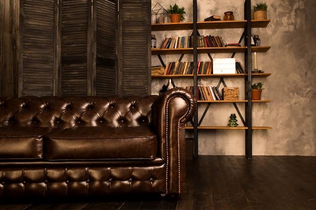 Brązowa skórzana sofa we wnętrzu pokoju z regałem.
