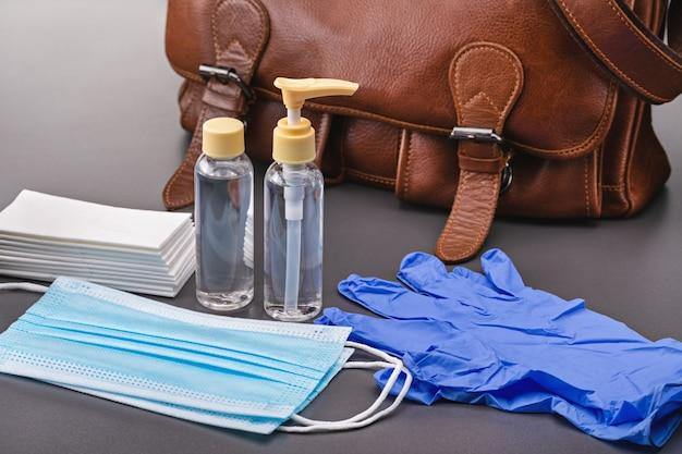 Brązowa skórzana torba. komplet sprzętu ochronnego podczas epidemii. maski medyczne, rękawiczki, chusteczki bakteriobójcze i spray antyseptyczny.