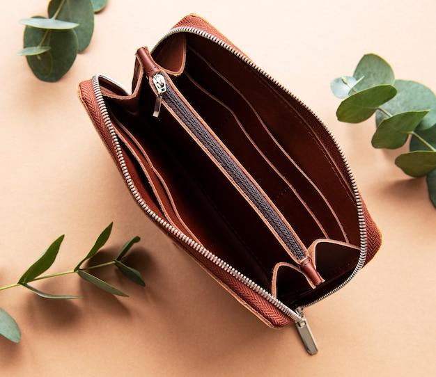 Brązowa skórzana torebka leżąca na jasnobrązowym stole, leżąca płasko.