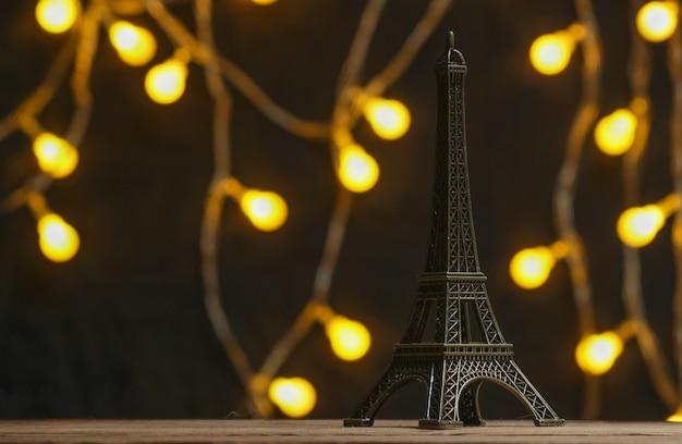 Brązowa statuetka wieży eiffla na ciemnym tle z girlandami.
