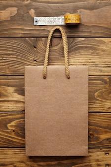 Brązowa torba na wynos z grubego makulaturowego papieru rzemieślniczego na rustykalnym drewnianym stole w pobliżu rocznika krawieckiego miernika