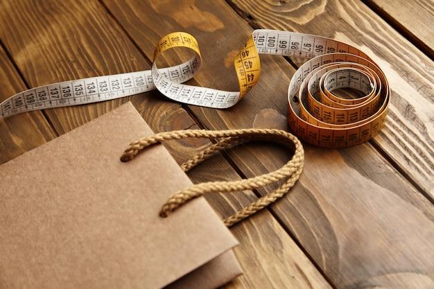 Brązowa torba na wynos z grubego papieru rzemieślniczego z recyklingu na rustykalnym drewnianym stole w pobliżu rocznika krawiectwa