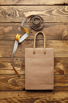 Brązowa torba na wynos z grubego papieru rzemieślniczego z recyklingu na rustykalnym drewnianym stole w pobliżu rozwiniętego rocznika krawieckiego miernika
