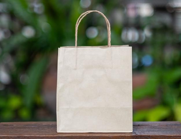 Brązowa torba na zakupy z makulatury umieszczona na drewnianym stole