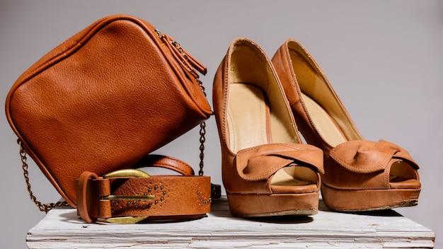 Brązowa torebka damska z butami i paskiem na białym tle na szarym tle
