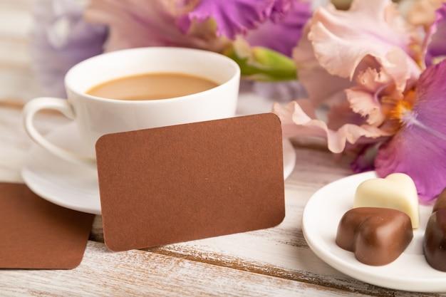 Brązowa wizytówka z filiżanką cioffee, cukierków czekoladowych i kwiatów tęczówki na białej powierzchni.