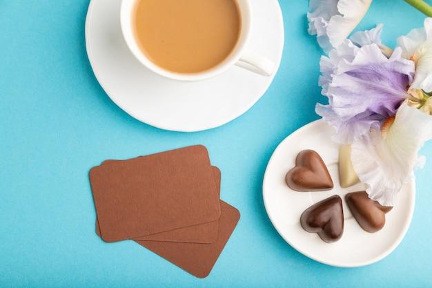 Brązowa wizytówka z filiżanką cioffee, cukierków czekoladowych i kwiatów tęczówki na niebieskim tle.