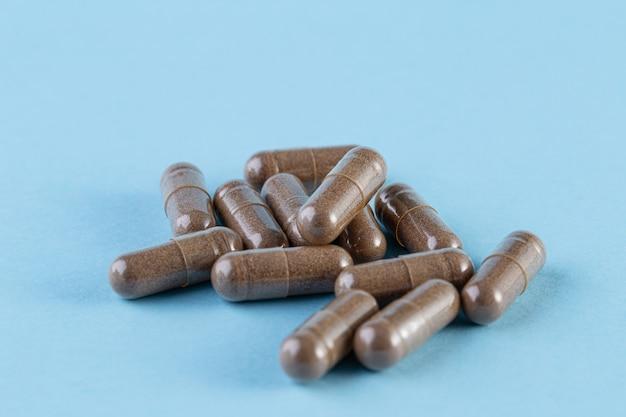 Brązowe antybiotyki kapsułki tabletki na pastelowym niebieskim tle.