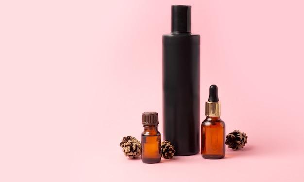Brązowe butelki olejków eterycznych i kosmetyków oraz szyszki na różowym tle.