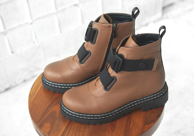 Brązowe buty damskie. kobiece obuwie jesienno-zimowe na drewnianym stojaku. nowoczesne zdjęcie projektowe