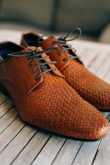 Brązowe buty męskie ze sznurowadłami na drewnianym tle