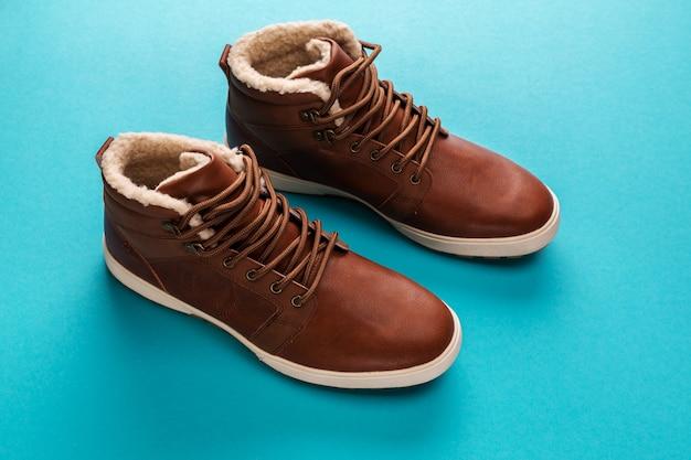 Brązowe buty męskie zimowe na niebieskim tle