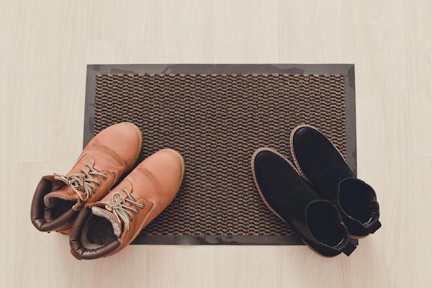 Brązowe damskie zamszowe i czarne buty na czarnym dywanie z napisem powitalnym.