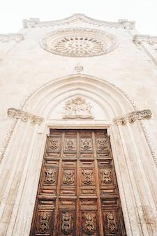Brązowe drewniane drzwi na białym betonowym budynku