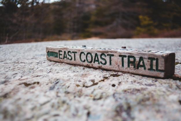 Brązowe drewniane powitanie na oznakowaniu plaży