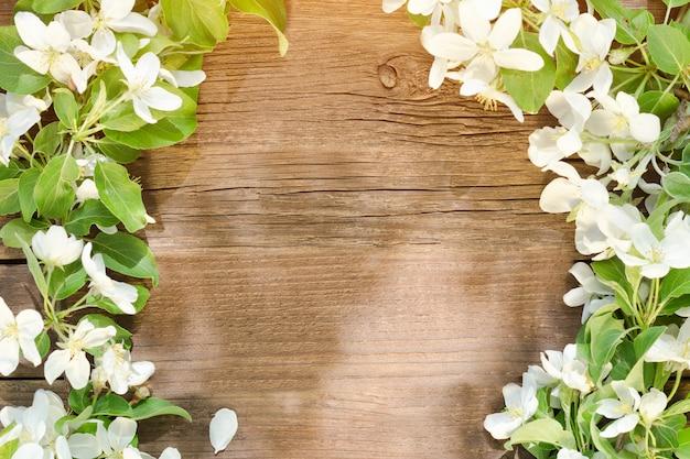 Brązowe drewniane tła. kwiaty jabłka na krawędzi ramy.