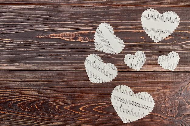 Brązowe drewniane tło z papierowymi sercami.