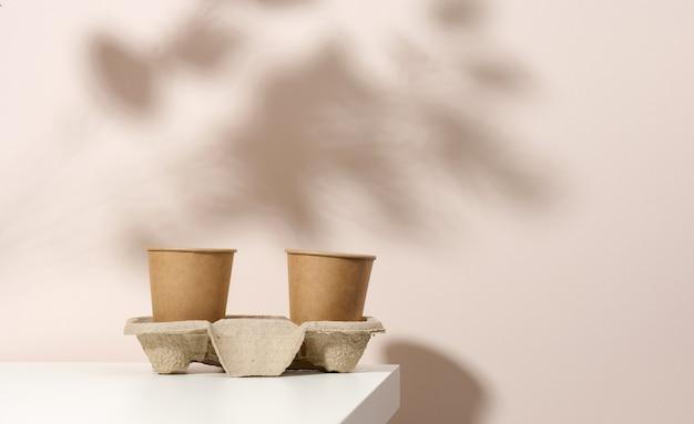 Brązowe ekologiczne jednorazowe papierowe kubki na białym stole