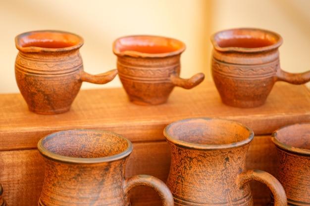 Brązowe gliniane doniczki ustawione są w rzędach. wykonany ręcznie