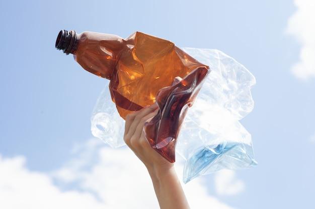 Brązowe i jasne plastikowe butelki są zmiażdżone i leżą w dłoni dziecka na tle błękitnego nieba z klockami.