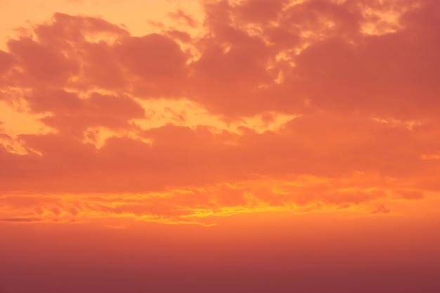 Brązowe i pomarańczowe niebo i chmury w tle widoku zachodu słońca