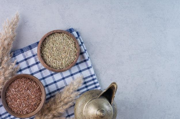 Brązowe i zielone suche nasiona anyżu w drewnianych kubkach.