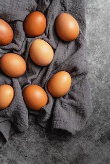 Brązowe jaja kurze na ciemnoszarym materiale, widok z góry na płasko