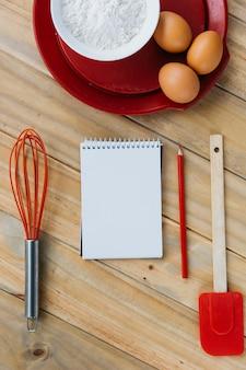 Brązowe jaja z mąki na tabliczce obok notatnika spirali; śmigać; ołówek i łopatka na powierzchni drewnianych