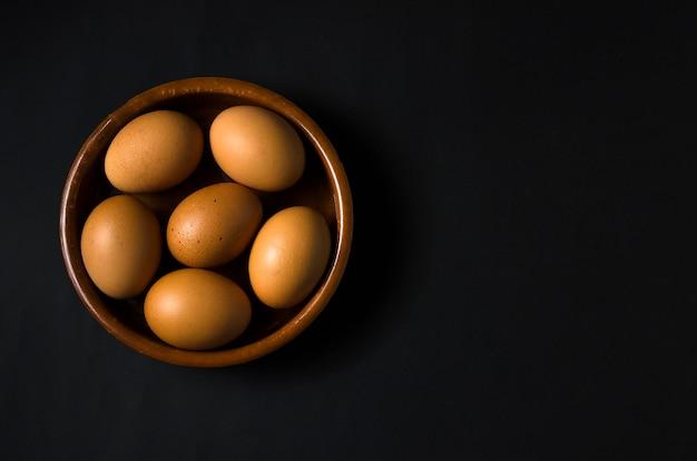 Brązowe jajka w brązowej misce odizolowanej na czarnym tle