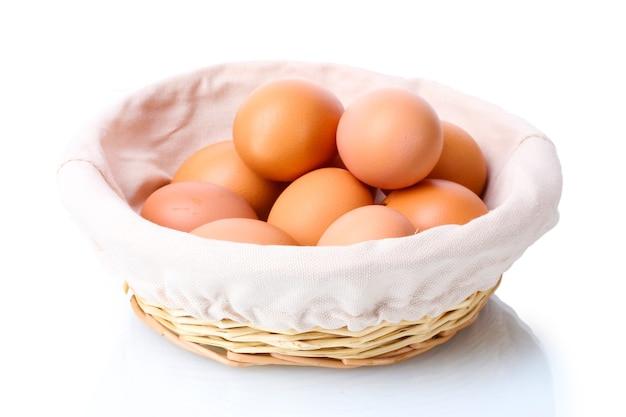 Brązowe jajka w koszyku na białym tle