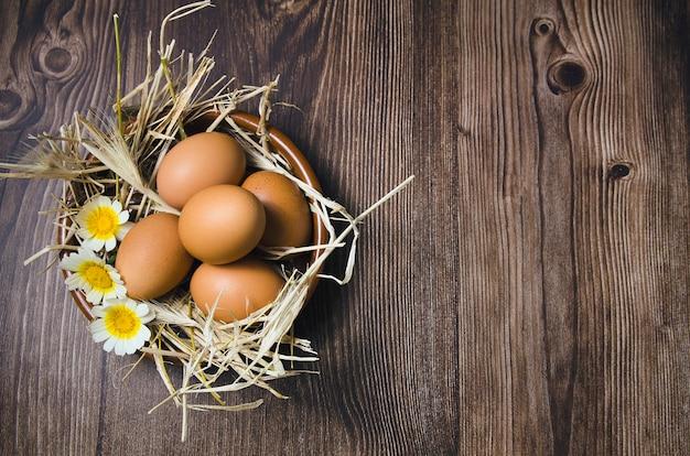 Brązowe jajka ze słomą i kwiatami w brązowej misce na drewnianym tle