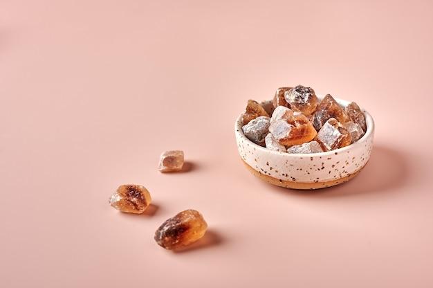 Brązowe karmelizowane kostki cukru trzcinowego w misce na różowym tle w proszku selektywnej kopii ostrości