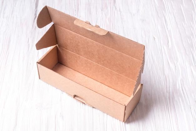 Brązowe kartonowe pudełko kartonowe, skrzynia na drewnianym biurku