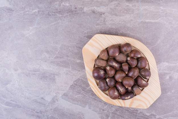 Brązowe kasztany w drewnianym talerzu na kamieniu