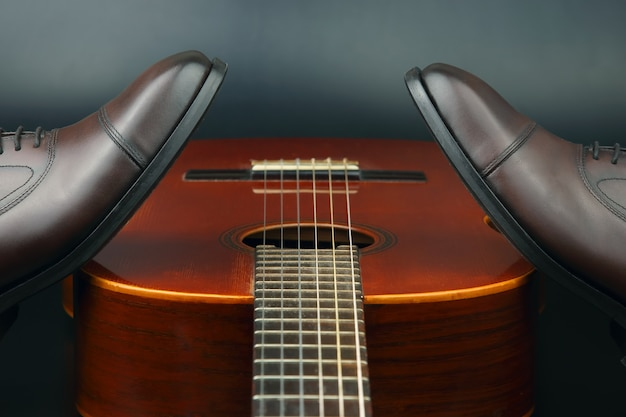 Brązowe klasyczne buty męskie na tle gitary klasycznej