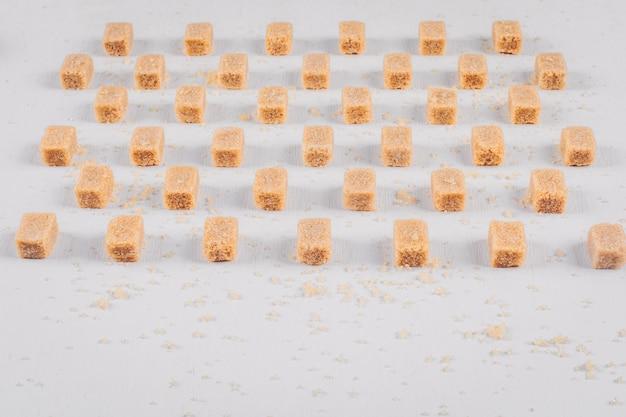 Brązowe kostki cukru ustawione w linii z dużym kątem widzenia